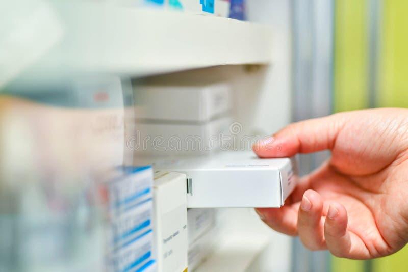 рука аптекаря держа коробку медицины в аптеке стоковые изображения