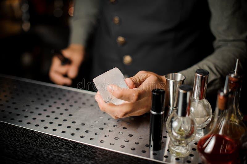 Рука бармена держа большую прямоугольную часть льда стоковые фотографии rf