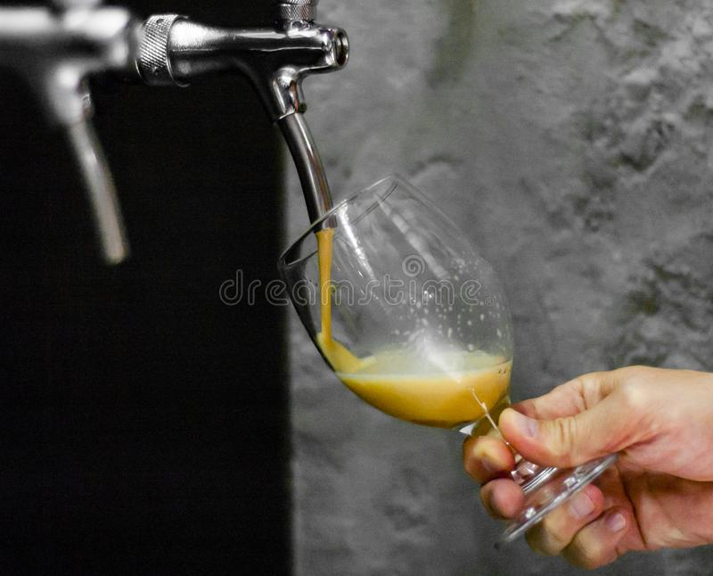 Рука бармена на кране пива лить пиво проекта в стеклянной сервировке стоковое фото rf