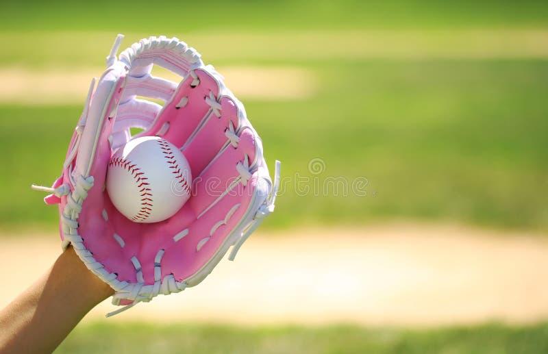 Рука бейсболиста с розовыми перчаткой и шариком стоковые фотографии rf