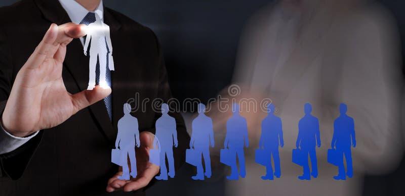 Рука бизнесмена выбирая значок людей стоковое изображение