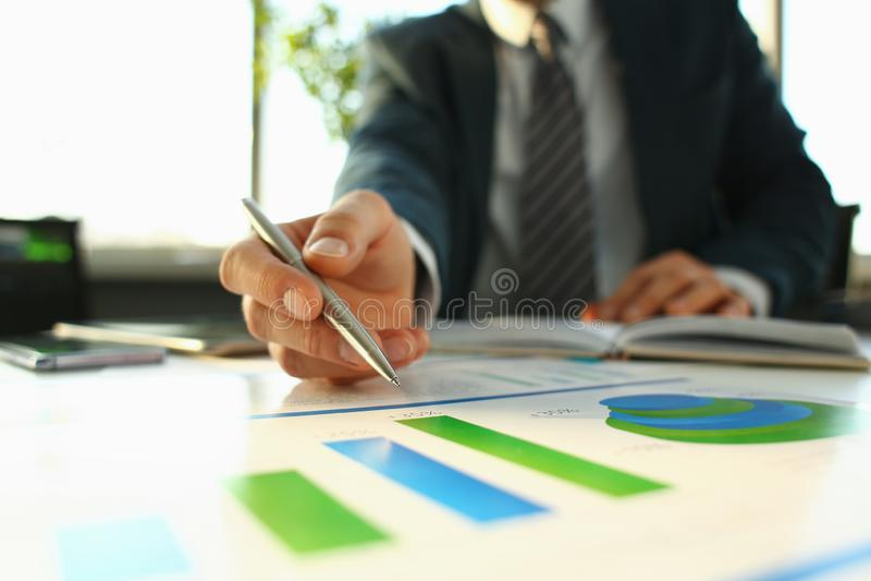 Рука бизнесмена в завалке костюма и подписания с стоковое фото
