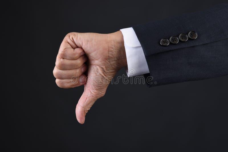 Рука бизнесмена давая большие пальцы руки вниз с крупного плана сигнала стоковое изображение