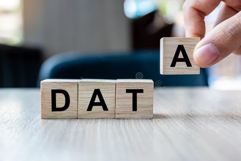 Рука бизнесмена держа деревянный блок куба со словом дела ДАННЫХ на предпосылке таблицы Концепции базы данных, финансовых и выход стоковое фото rf