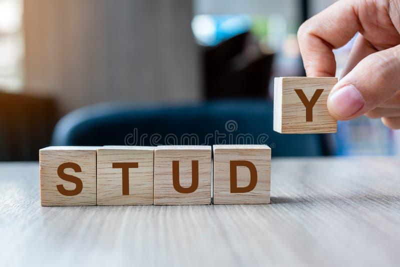 Рука бизнесмена держа деревянный блок куба со словом дела ИССЛЕДОВАНИЯ на предпосылке таблицы Конкретное исследование, учить и мо стоковая фотография