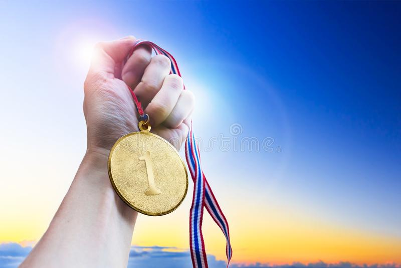 Рука бизнесмена держа золотое медаль монетки стоковое изображение rf