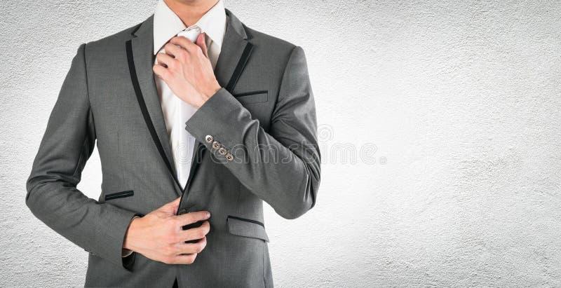 Download Рука бизнесмена держа галстук в серой сюите на конкретном Cbac Стоковое Фото - изображение насчитывающей конец, экзекьютив: 81811820