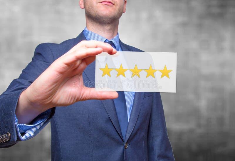 Рука бизнесмена держа 5 звезд изолированный на серой предпосылке стоковые фотографии rf