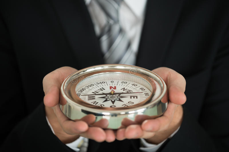 Рука бизнесмена держа компас стоковые фото