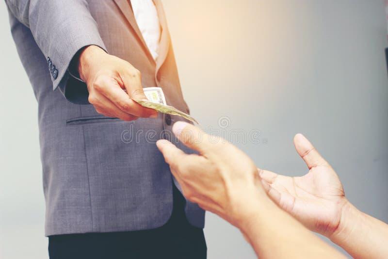 Рука бизнесмена держа доллар США, USD счеты, деньги банкноты доллара предложений и деньги давать оплатили для что-то мимо получаю стоковое изображение