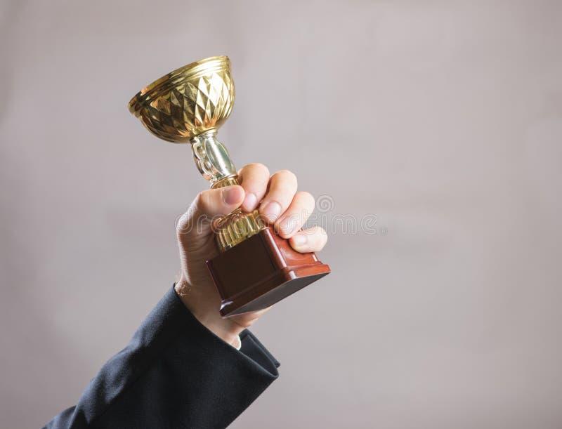Рука бизнесмена держа чашку, успех концепции стоковая фотография rf