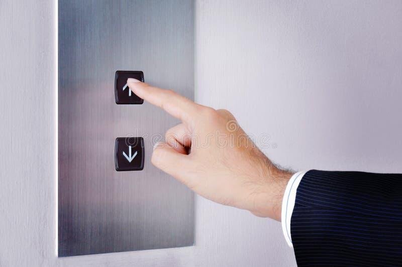 Рука бизнесмена касаясь идти вверх знак на пульте управления подъема стоковое изображение