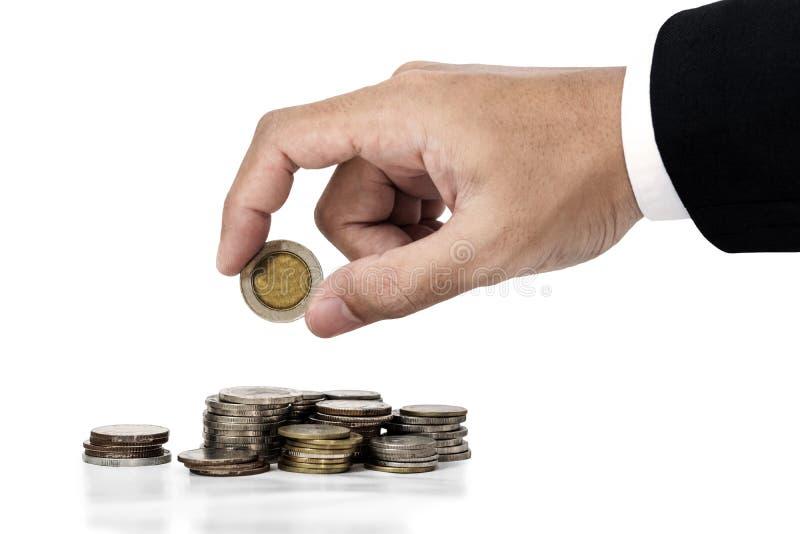Рука бизнесмена кладя деньги чеканит, сохраняющ изолированную концепцию денег, на белой предпосылке стоковая фотография rf