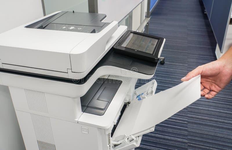 Рука бизнесмена положила лист чистого листа бумаги в принтер input для копируя и просматривая документов стоковые изображения