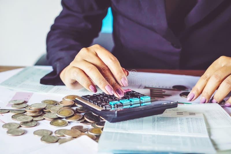 рука бизнес-леди высчитывая ее ежемесячные расходы во время налога приправляет с монетками, калькулятором, стоковые изображения rf