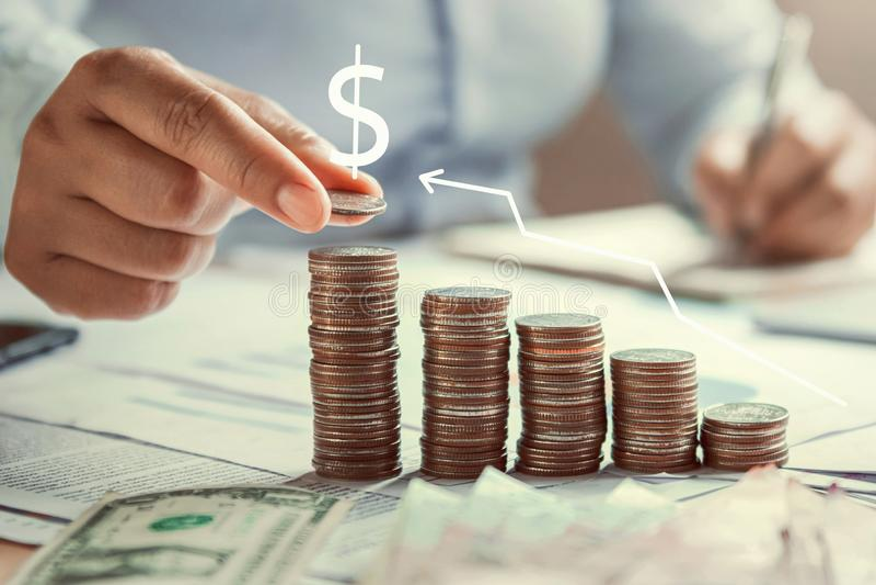 рука бизнес-леди держа монетки для того чтобы штабелировать на финансах денег концепции стола сохраняя стоковые изображения rf