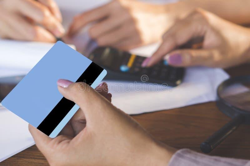 Рука 2 бизнес-леди рассчитывать калькулятор и держа кредитную карточку, взыскание долгов и ходить по магазинам онлайн стоковое изображение rf