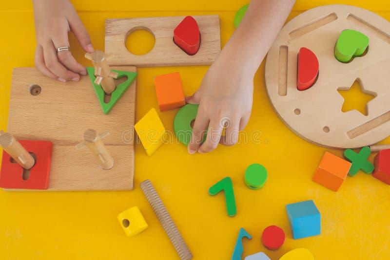 Рука взгляд сверху милой маленькой девочки играя детей забавляется в комнате детства стоковая фотография