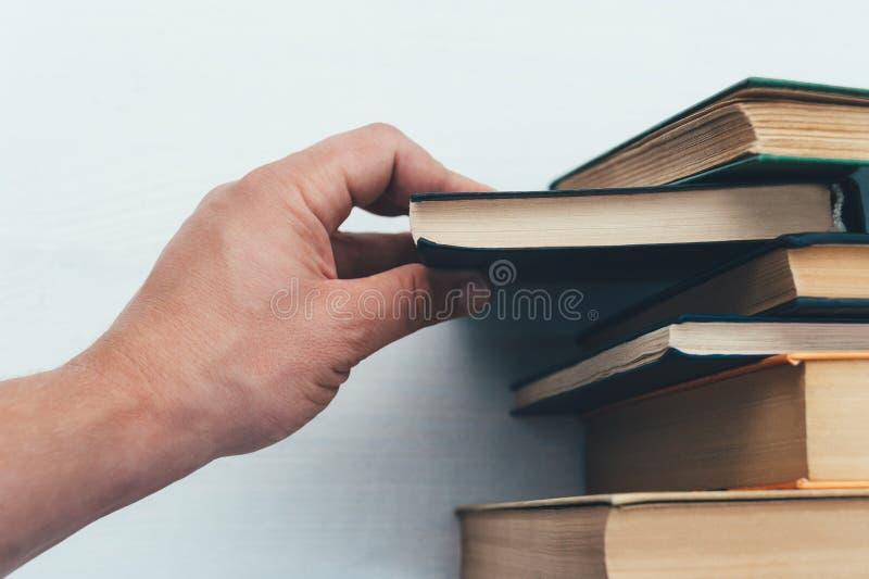 Рука вытягивает книгу, от bookcase стоковая фотография rf