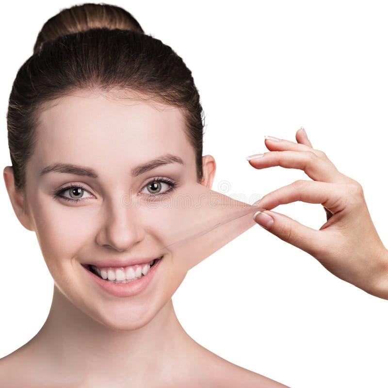 Рука вытягивая кожу от щеки молодой женщины стоковые фото