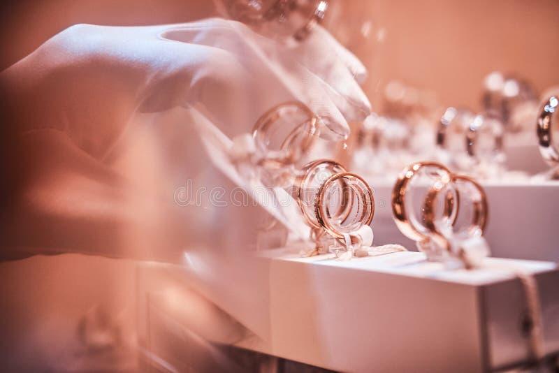 Рука в перчатках принимает к исключительным кольцам на витрине ювелирного магазина стоковое изображение rf