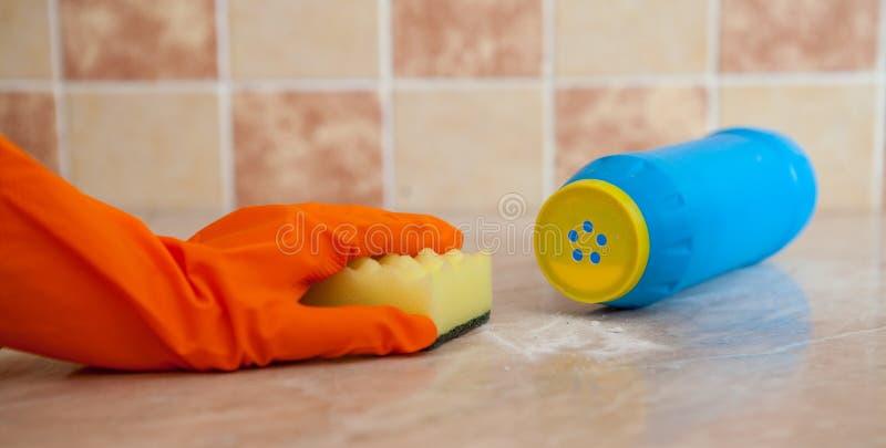 Рука в перчатках orenge резиновых моет поверхность с мягкой желтой губкой около поцарапанного тензида стоковая фотография rf