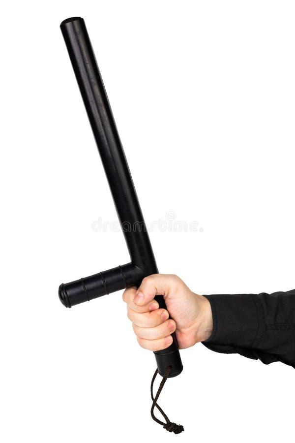 Рука в черной рубашке с черным резиновым жезлом полиции изолированным на белой предпосылке стоковое изображение