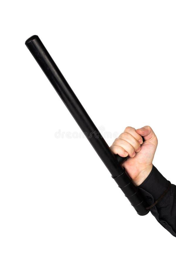 Рука в черной рубашке с черным резиновым жезлом полиции изолированным на белой предпосылке стоковое изображение rf