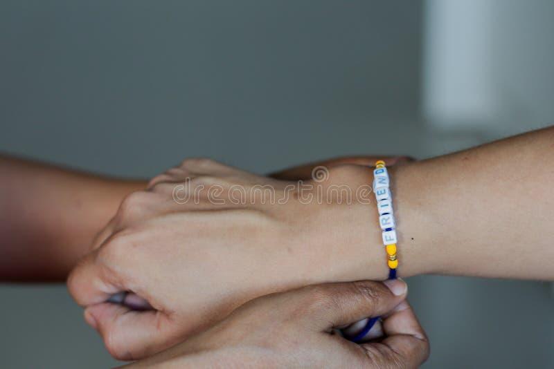 рука дамы связывая диапазон приятельства в руке парня с выборочным фокусом стоковое фото
