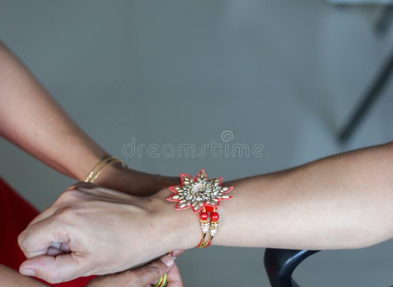 рука дамы связывая rakhi в руке парня во время индусского ритуала rakshabandhan с выборочным фокусом стоковое изображение rf