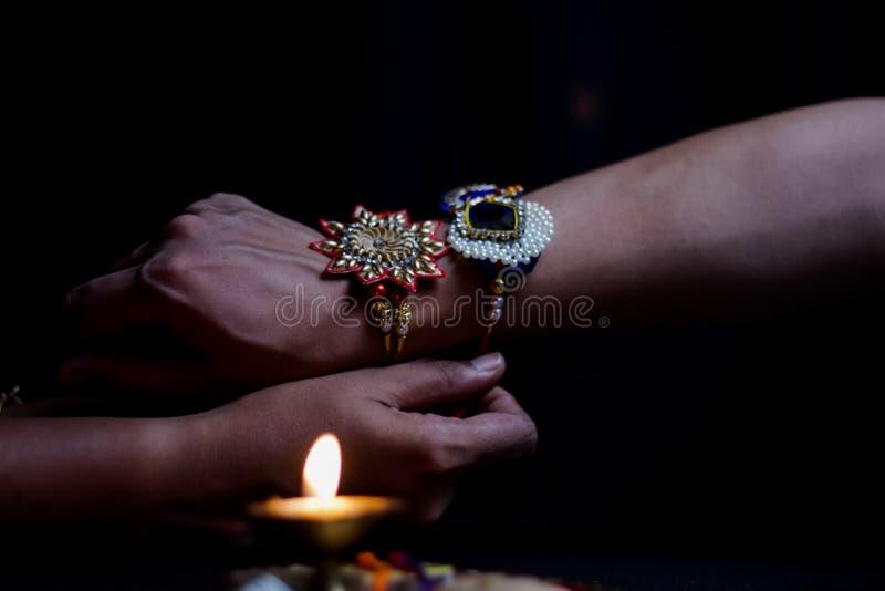 рука дамы связывая rakhi в руке парня во время индусского ритуала rakshabandhan с выборочным фокусом стоковые фотографии rf
