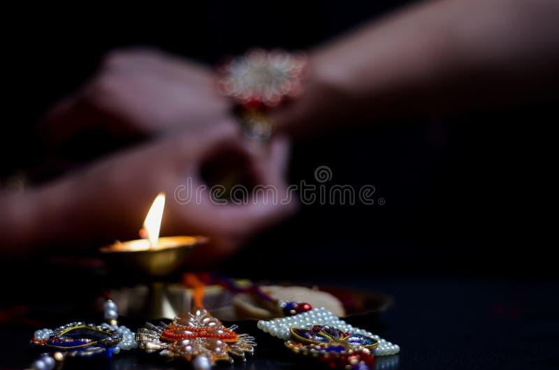 рука дамы связывая rakhi в руке парня во время индусского ритуала rakshabandhan с выборочным фокусом стоковая фотография