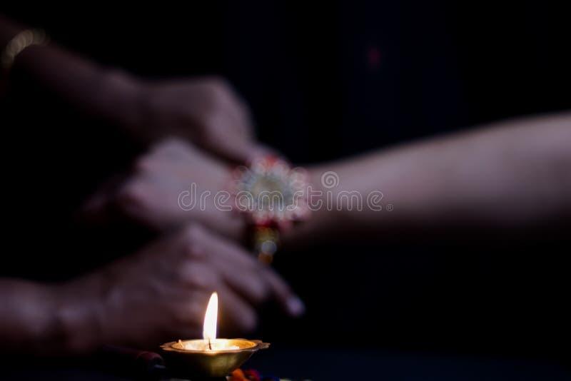 рука дамы связывая rakhi в руке парня во время индусского ритуала rakshabandhan с выборочным фокусом стоковые изображения