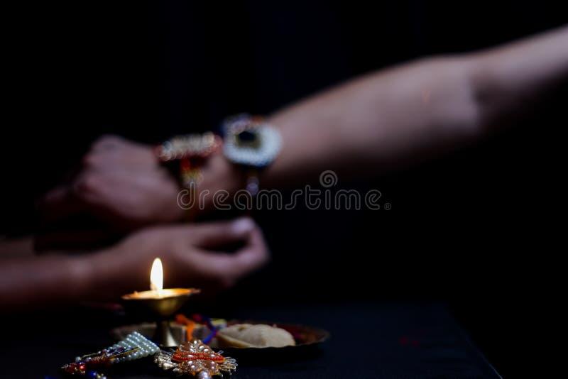 рука дамы связывая rakhi в руке парня во время индусского ритуала rakshabandhan с выборочным фокусом стоковое фото