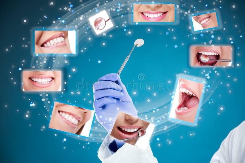 Рука дантиста с зеркалом и идеальными улыбками стоковое фото rf