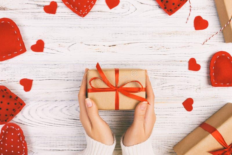 Рука девушки дает подарочную коробку Валентайн с красной внутренностью сердца на белом тонизированном, винтажном старом деревянно стоковые изображения rf