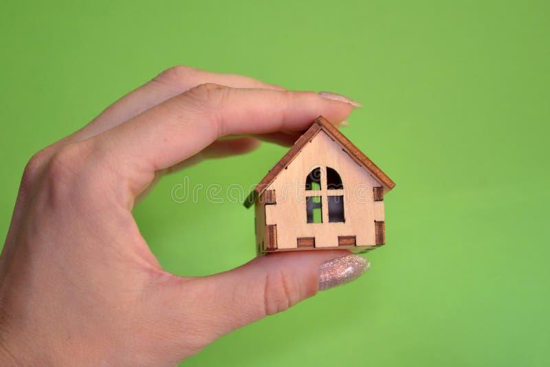 Рука девушки держа деревянный миниатюрный дом игрушки на свете с зеленой предпосылкой, с copyspace стоковые фотографии rf