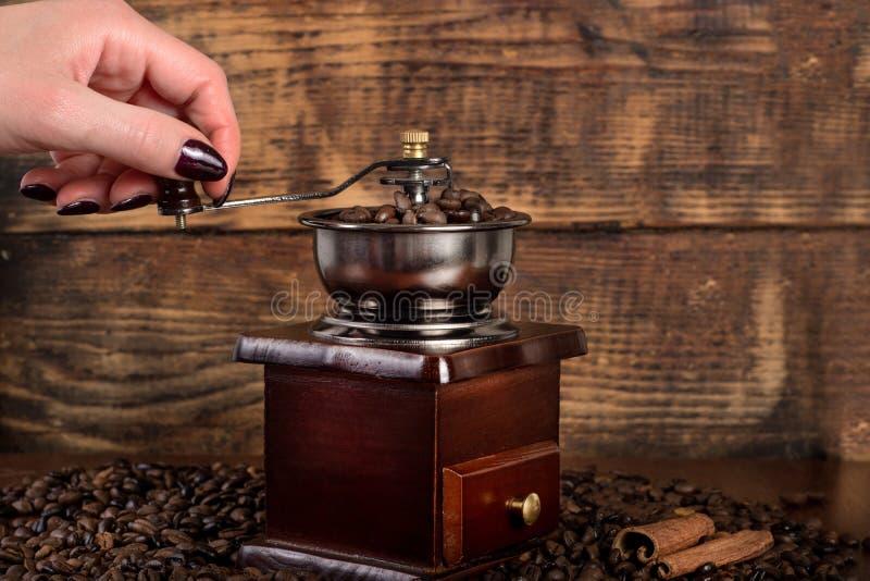 Рука девушки меля в старой мельнице зажарила в духовке кофейные зерна на деревянной предпосылке стоковые изображения rf