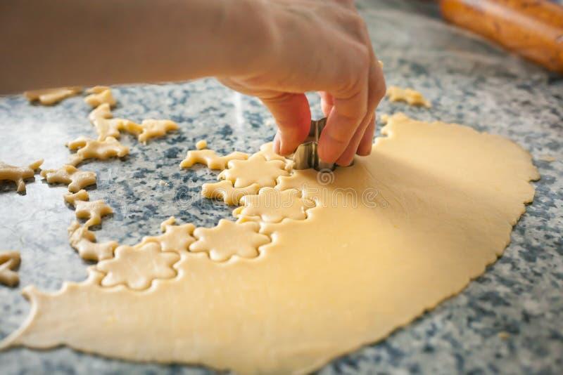 Рука делая формы в выдвинутом тесте на кухонном столе делая сезонную еду печенья стоковое изображение rf