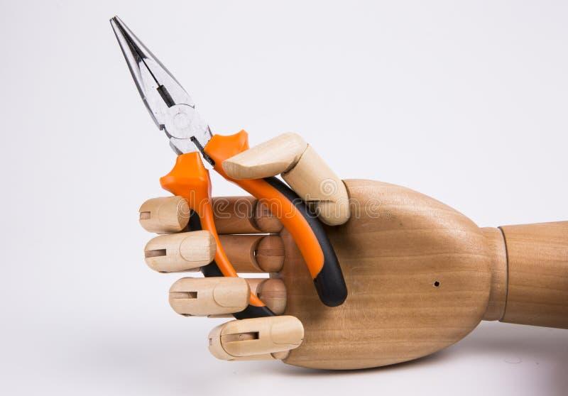 Рука держащ плоскогубцы стоковое изображение