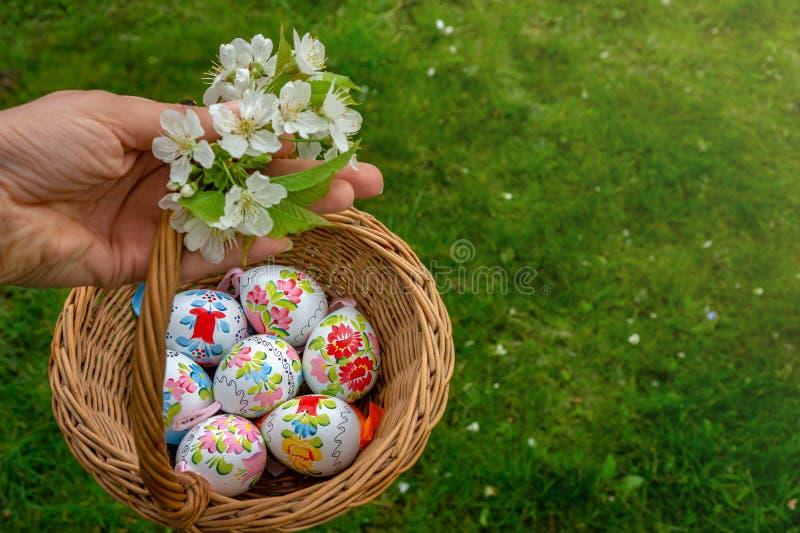 Рука держа близко вверх красочной руки покрасила пасхальные яйца в ко стоковые изображения rf