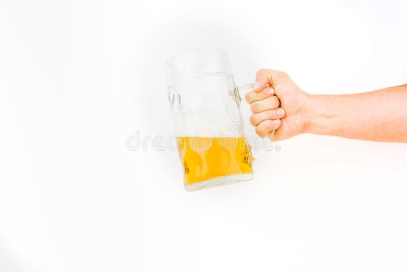 Рука держа большую кружку светлого пива стоковые изображения