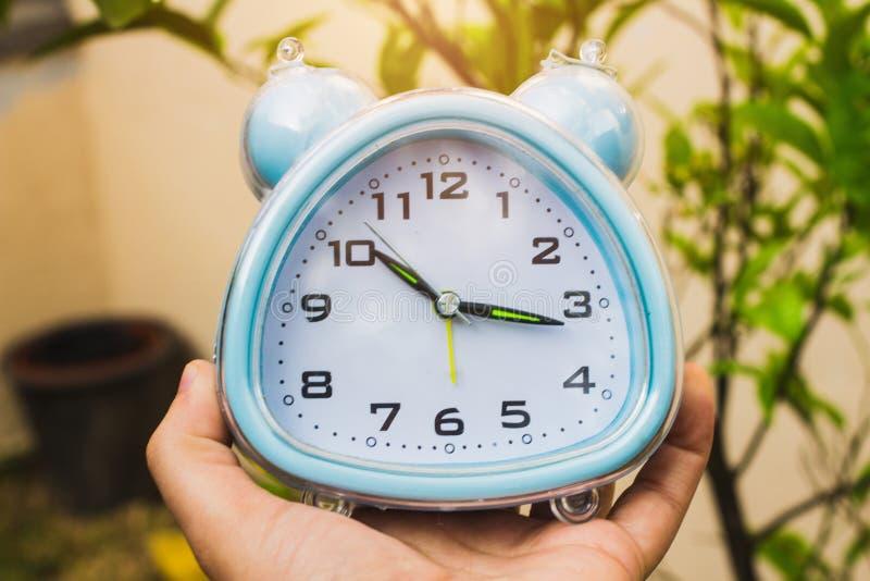Рука держа будильник стоковое изображение