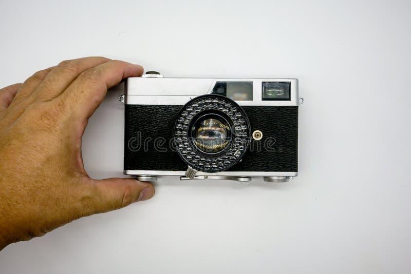 Рука держа винтажную камеру дальномера изолированный на белизне стоковые фотографии rf