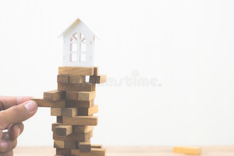 Рука держа деревянный блок с модельным Белым Домом на игре деревянного блока Инвестиционный риск и неопределенность в снабжении ж стоковое изображение rf