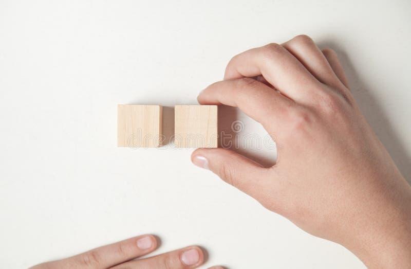 Рука держа деревянный куб на белом столе стоковые изображения rf