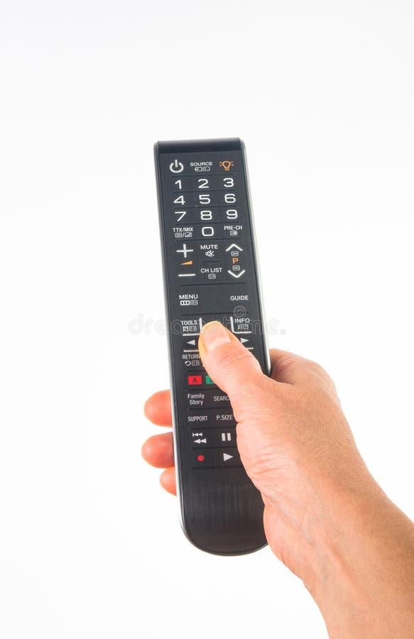 рука держа дистанционное управление на белой предпосылке, конце-вверх стоковое фото