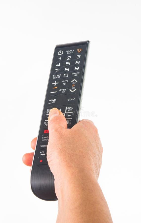рука держа дистанционное управление на белой предпосылке, конце-вверх стоковое фото rf