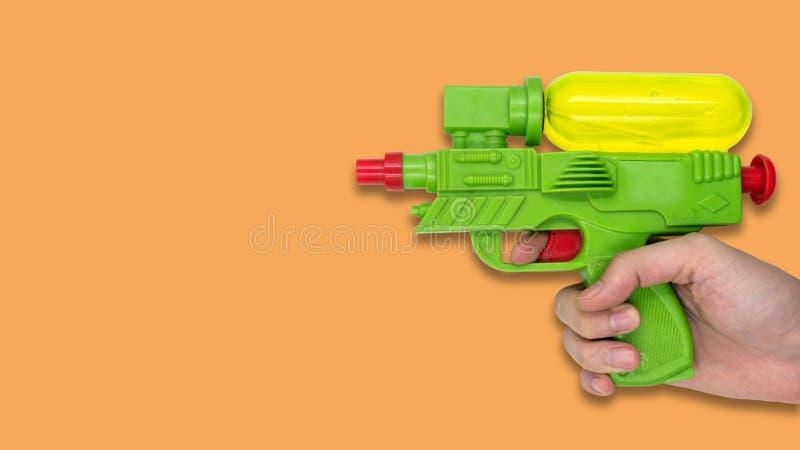 Рука держа игрушку воды оружия на оранжевой предпосылке Открытый космос для текста стоковые фотографии rf