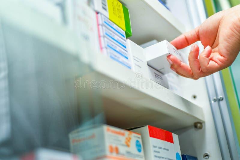 Рука держа коробку медицины в аптеке фармации стоковое фото